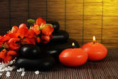 Spa stones with flowers and candles on bamboo background — Stock Photo