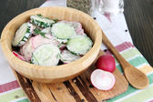 Vitamin vegetable salad in wooden bowl on wooden table close-up — Stock Photo
