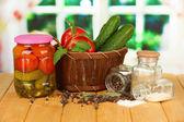 Délicieux concombres verts et des tomates rouges dans le panier, sur une table en bois sur fond clair — Photo