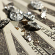 Beautiful shining crystals (diamonds) on money background — Stock Photo