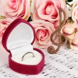 Treble clef, roses and box holding wedding ring on musical background — Stock Photo #25411019