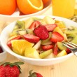 Useful fruit salad of fresh fruits and berries in bowl on wooden table close-up — Stock Photo