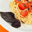 Spaghetti with tomatoes and basil leaves on wooden background — Stock Photo #25412767