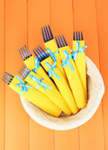 Blue plastic forks wrapped in yellow paper napkins, in basket, on color wooden background — Stock Photo