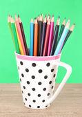 Lápis coloridos na copa na mesa sobre fundo verde — Fotografia Stock