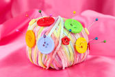 Colorful buttons and multicolor wool ball, on color fabric background — Stock Photo