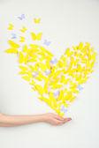 Mariposa de papel amarillo en forma de corazón en pared — Foto de Stock
