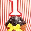 Birthday cupcake with chocolate frosting on striped background — Stock Photo