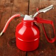 Stock Photo: Red oil can, on wooden background