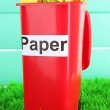 Recycling bin with papers on grass on light blue background — Stock Photo #25450269