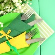 Forks and knives wrapped in green and yellow paper napkins, on color wooden background — Stock Photo #25450555