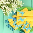Blue plastic forks wrapped in yellow paper napkins, on color wooden background — Stock Photo #25450657