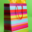 Striped shopping bag on green background — Stock Photo