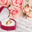 Treble clef, roses and box holding wedding ring on musical background — Stock Photo #25452389