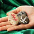 Stock Photo: Fortune telling with symbols on stone in hand on green fabric background