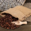 Coffee beans in sack on wooden background — Stock Photo