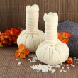 Stock Photo: Herbal compress balls for sptreatment and towel on bamboo background
