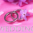 Beautiful wedding rings on pink background — Stock fotografie