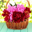 Beautiful peonies in wicker basket on table on bright background — Stock Photo