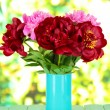Beautiful peonies in vase on table on bright background — Stock Photo