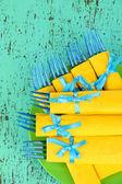 Tenedores de plástico azules envuelven en servilletas de papel amarillo, sobre fondo de madera color — Foto de Stock