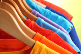 Lots of T-shirts on hangers on green background — Stock Photo