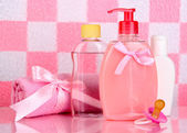 Baby cosmetics and towel in bathroom on pink tile wall background — Stock Photo
