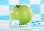 Apple with a toothbrush on shelf in bathroom — Stock Photo