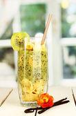 Delicious fruit smoothie on wooden table on window background — Stock Photo