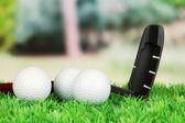 Golfové míčky a řidič na zelené trávě venkovní zblízka — Stock fotografie
