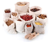 Different kinds of beans in sacks isolated on white — Stock Photo