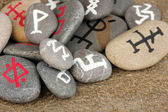 Fortune telling with symbols on stones on burlap background — Stock Photo
