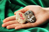 Fortune telling with symbols on stone in hand on green fabric background — Stock Photo
