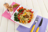Noodles with vegetables on plate on wooden table — Stock Photo
