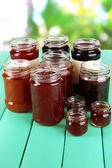 Tasty jam in banks on table on bright background — Stock Photo