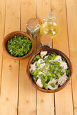 Boiled meat on wooden bowl and herbs on wooden table — Stock Photo