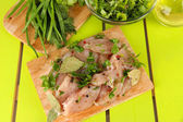 Chicken meat in glass plate,herbs and spices on wooden table — Stock Photo