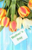 Mooi wit en oranje tulpen op een houten achtergrond kleur — Stockfoto