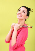 Beautiful young woman painter with brushes, on color background — Stock Photo