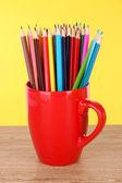 Kleurrijke potloden in cup op tabel op gele achtergrond — Stockfoto