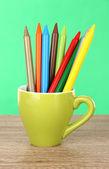 在绿色背景上桌上的杯子彩色铅笔 — 图库照片