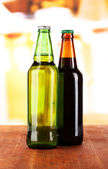 Bier in bottles on table on room background — Stock Photo