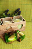Candles in wooden candlestick, lavender and soap, on green mat — Stock Photo