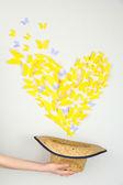 Papier gelb schmetterling in form von herzen fliegen hut — Stockfoto