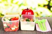 在塑料容器中,在明亮的背景上竹垫上美味的午餐 — 图库照片