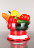 Fresh vegetables in scales on gray background — Stockfoto