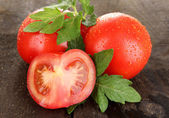 Fresh tomatoes on wooden table close-up — Stock Photo