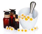 Esenciální olej a květy heřmánku v třecí misce izolovaných na bílém — Stock fotografie