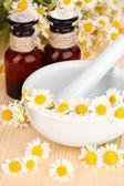 Esenciální olej a květy heřmánku v moždíři na dřevěný stůl — Stock fotografie