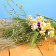 Stock Photo: Bouquet of wild flowers and herbs, on wooden table on color background